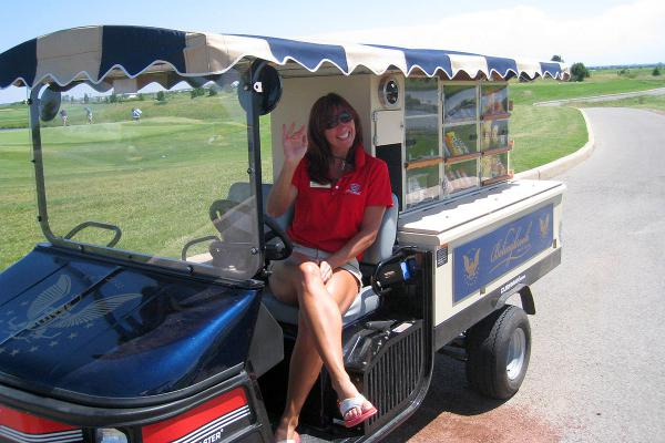 Smiling woman sitting in drivers seat of golf course drink cart.