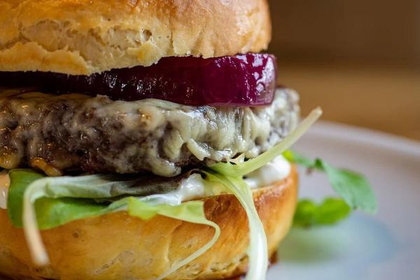 Cheesburger with lettuce and red onion on a plate.