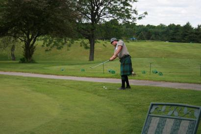 Golpher practicing chipping on the practice green at the Hickory Dickory Decks Charity Golf Tournament.